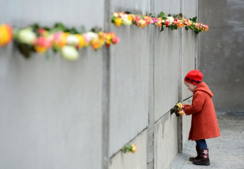 A young girl slips a rose in a preserved segment of the Berlin Wall during the commemorations to mark the 25th anniversary of the fall of the Berlin Wall at the Berlin Wall Memorial in the Bernauer Strasse in Berlin, on November 9, 2014.
