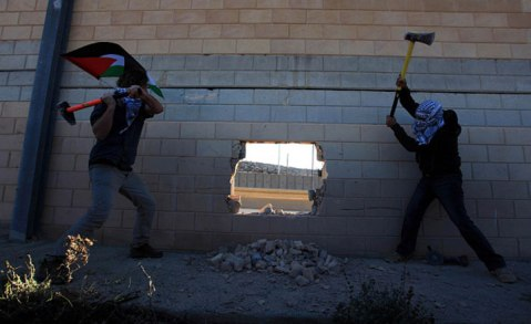 Palestinians make a hole in Israeli West Bank barrier, separating Israel and the West Bank, one day before the 25th anniversary of the fall of Berlin Wall near Bi'r Nabala neighborhood of Ramallah, West Bank on November 08, 2014.